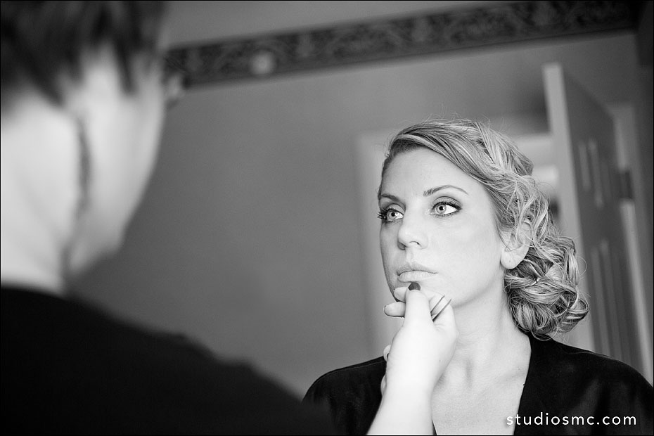 B&W photo of a bride getting her makeup done